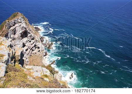 Aerial top view of sea waves hitting surrounded by rocks spot next to Cape of Good Hope, Cape Town, South Africa.