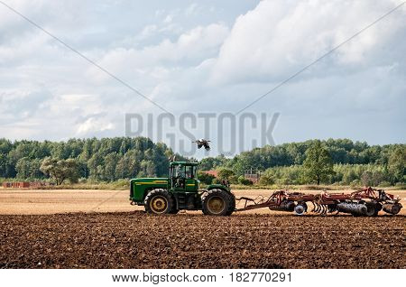 DOBELE LATVIA - AUGUST 9 2011: Green tractor processes the ground for the new harvest.