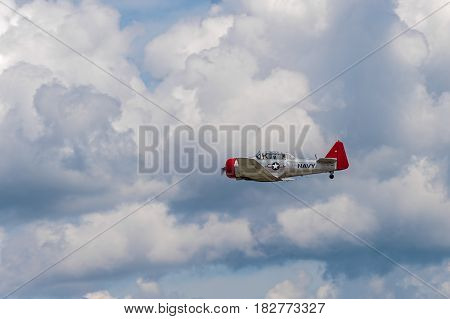 EDEN PRAIRIE MN - JULY 16 2016: AT-6G Texan airplane flies by through cloudy sky at air show. The AT-6 Texan was primarily used as trainer aircraft during and after World War II.