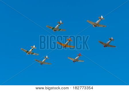 EDEN PRAIRIE MN - JULY 16 2016: Seven AT6 Texan airplanes fly overhead in clear blue sky at air show. The AT6 Texan was primarily used as trainer aircraft during and after World War II.
