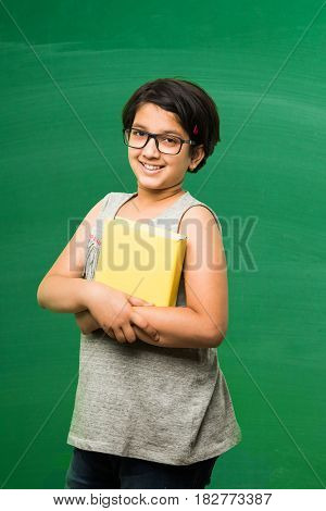 education and indian girl concept - cute little indian girl or schoolgirl holding books and posing in front of camera over green chalkboard background with doodles on it