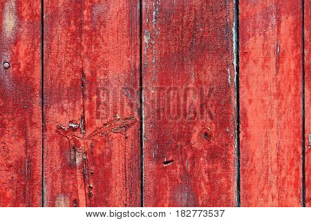 Texture of old painted boards, painted old wooden wall, surface texture of the boards with the old red  paint, old shabby wooden planks with cracked color paint, old board with peeling paint red