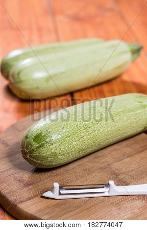 Fresh Raw Zucchini On The Wooden Board With Knife Peeler