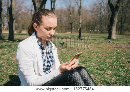 Beautiful young European girl sits on the grass in the park and uses a smartphone, concepts of using gadgets in a natural environment in the fresh