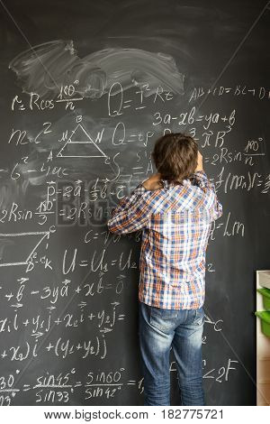 Teenageer Boy with chalk writting complicated math formulas on black board