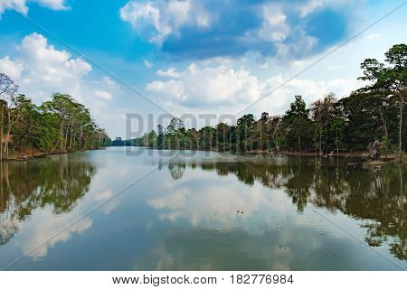 Beautiful lake nestled among rainforest in Cambodia under blue sky with white clouds. It surrounding mysterious ruins of Angkor Thom in Siem Reap, Cambodia.