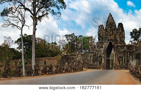 South gate to Angkor Thom and the faces of stone giants guarding the entrance, Siem Rea,p Cambodia. The road to the Angkor Thom