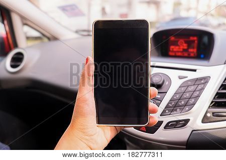 Close up Young female driver using touch screen smartphone and gps navigation in a car concept using smart phone in car.