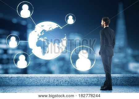 Young businessman on concrete rooftop with night city view abstract digital HR icons and globe. Network concept