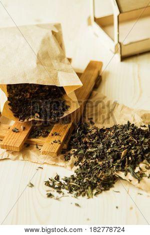 Loose tea in paper bag on wooden background