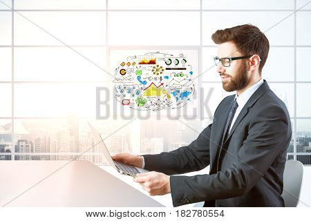 Side view of young businessman using laptop in modern office with desktop and panoramic city view. Communication concept. 3D Rendering