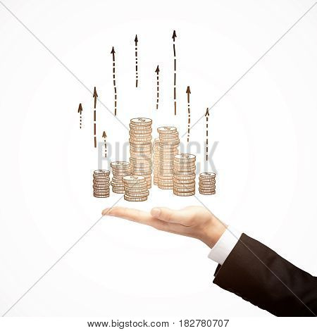 Businessman holding abstract drawn coins with upward arrows. Financial growth concept. Close up. White background