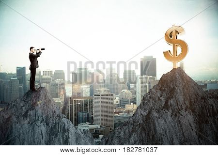 Side view of young businessman on cliff looking at dollar sign through binoculars. Wealth concept. City background