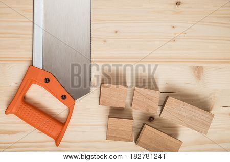 Hand saw with orange handle and sawn-off board. On wooden background.