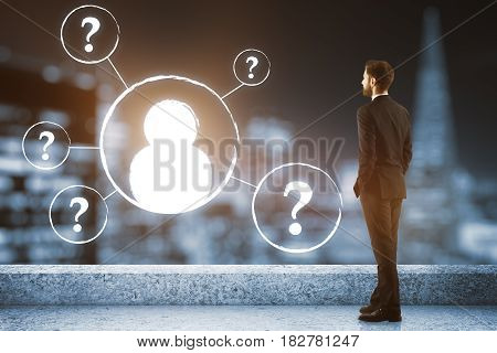 Young businessman on concrete rooftop with night city view and abstract digital HR icons. Employer concept