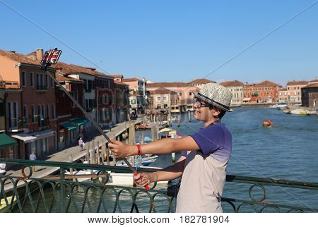 young teenage boy smiles while he takes a picture by his smartphone on the bridge of the island near Venice in Italy