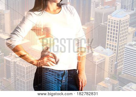 Young woman with hand on side standing on creative city background with sunlight. Success concept. Double exposure