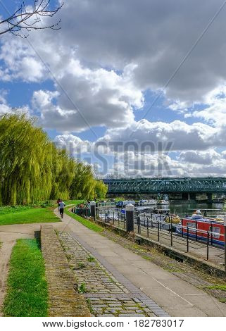 Towpath with joggers by River Lea Bow London. Shows willow trees and railway bridge in spring.