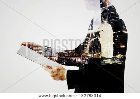 Side view of businessman with document standing on abstract night city background. Employment concept. Double exposure