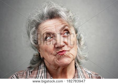 Smile and thinking grandmother face on a grey background
