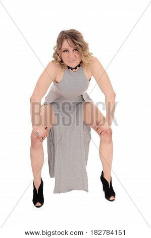 A beautiful young woman in a gray dress and heels standing and bending forwards showing her legs isolated for white background.