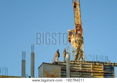 Ternopil, UKRAINE - April 21, 2017: Workers during formwork for concrete pouring with metal rebar rods at building site. Developer concept.