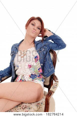 A beautiful young woman in a baby doll night gown sitting in an old armchair with a jeans jacket isolated for white background.