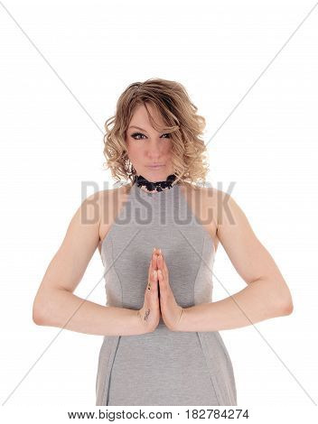 A lovely blond woman standing in a gray dress with her hands folded praying isolated for white background.