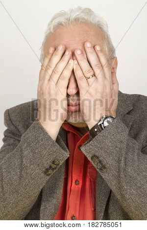 Senior hands his face - on bright background