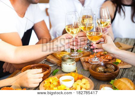 Hands With Red Wine Toasting Over Served Table With Food.