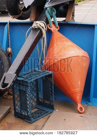 Blue plastic box and orange fender on a fishing boat.