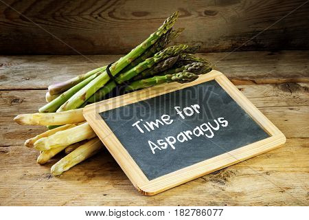 Green and white asparagus and a blackboard with the text time for asparagus on a rustic wooden background selective focus narrow depth of field