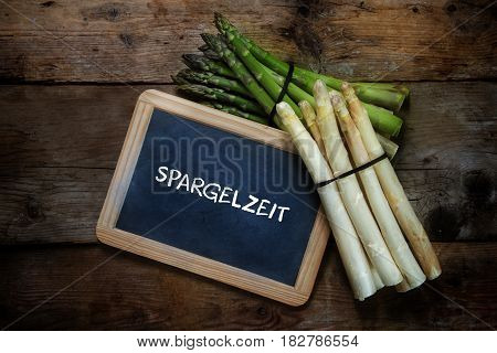 Green and white asparagus and a blackboard with german text Spargelzeit that means asparagus time on a rustic wooden background top view from above copy space selective focus