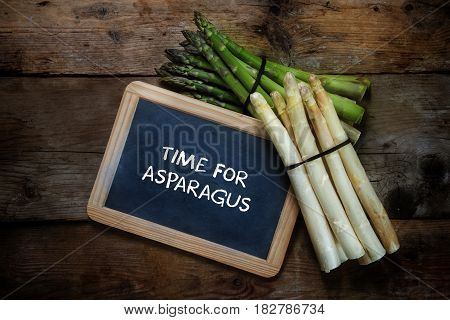 Green and white asparagus and a blackboard with text time for asparagus on a rustic wooden background top view from above copy space selective focus
