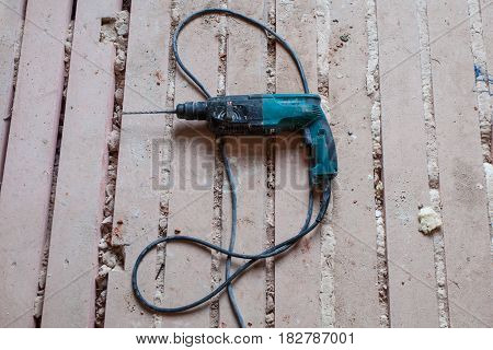 Electric perforator is on the dirty and dusty wooden floor during under renovation remodeling and construction of apartment.
