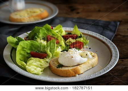 Poached egg on baguette slice with salad and tomatoes white plate on a dark rustic wooden table delicious breakfast or snack selective focus narrow depth of field