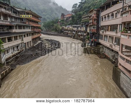 Wulai Taiwan - October 09 2016: Landscape of buildings on a misty rainy and lush hill by a river in Wulai