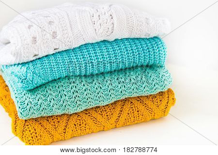 Stack of Cozy Cotton Knitted Sweaters on White Background