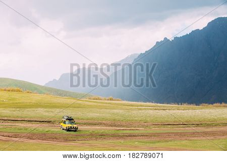 Yellow SUV Car On Off Road In Spring Mountains Landscape In Georgia. Drive And Travel Concept. Landscape Of Gorge At Spring Season.