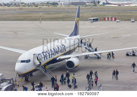 VALENCIA, SPAIN - APRIL 21, 2016: Passengers debarking a Ryanair flight. In 2016, Ryanair was the largest European airline by scheduled passengers carried.