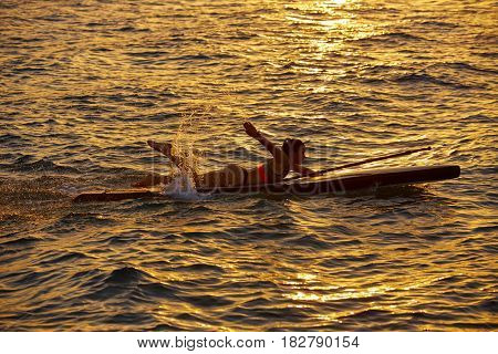 SUP Stand up Surf girl swimming lying on board at sunset