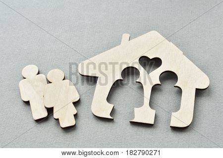 wooden house shape over grey background with man and woman outside