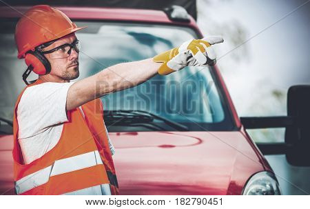 Road Work Supervisor in Front of Company Van Showing Other Workers Place to Start Their Work.