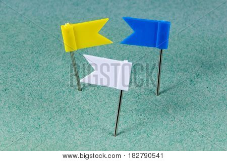 Yellow Blue and White flag pins on a green background