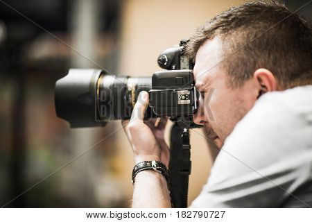 Studio Photographer in Action. Caucasian Photographer Taking Picture Using Professional Photo Gear.