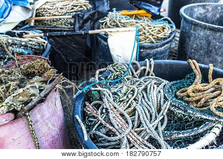 Bunch of colorful nautical ropes and nets close by the docks of a fishing harbor