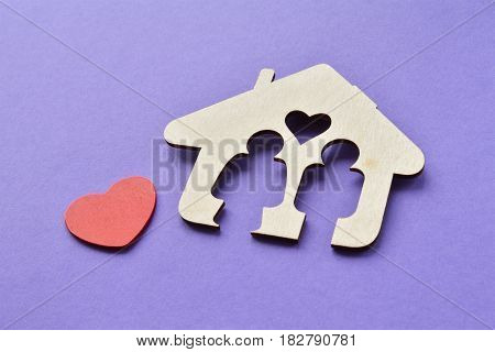wooden house with red heart, man and woman inside, love and happy family concept