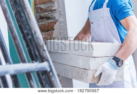 Construction Worker Moving Concrete Materials For House Interior Remodeling.