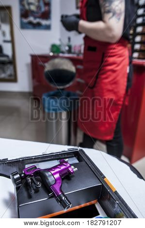 Gun ink machine ready for use at tattoo studio. Vertical shot
