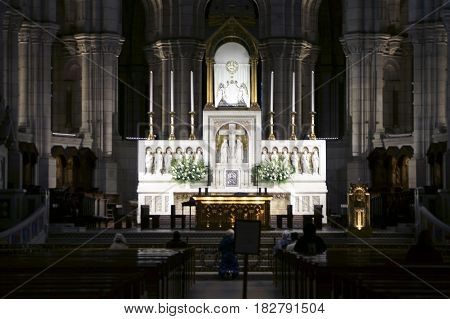 PARIS, FRANCE - DECEMBER 29: People praying at the illuminated altar of the Sacré-C